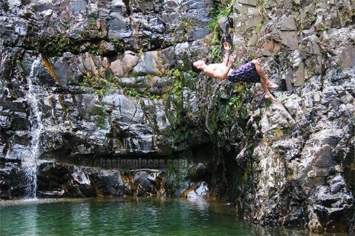An adventurous tourist backflipping into the fall's pool.