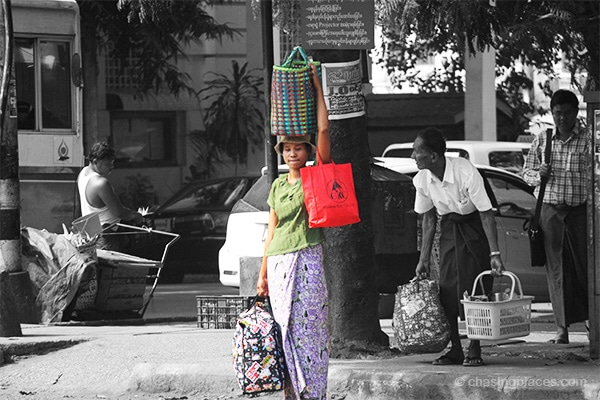 Three bags, two arms and one neck. This woman waits patiently in the humid heat of Yangon for a bus to arrive.