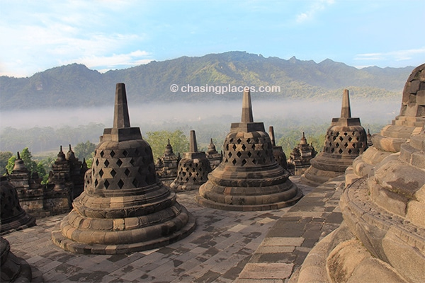 The morning mist rising over the surrounding mountain ridges at Borobudur.