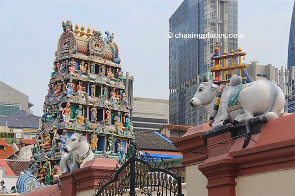 Sri Mariamman Temple designs in the foreground and urban skycrapers in the background.