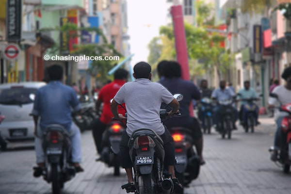 Local Maldivians driving along the narrow streets of Male.