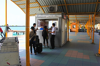 Proceed to the ferry ticket counter outside the airport
