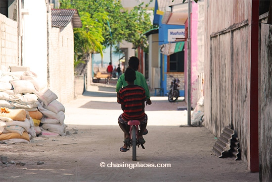 A couple of the young-Maldivian locals briskly cycling along the sandy road