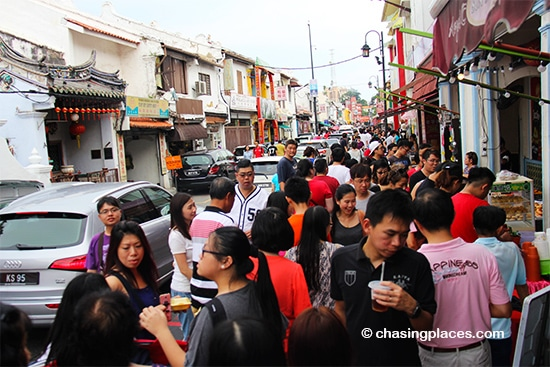 Cars squeezing through the Jonker Walk's tourist crowd