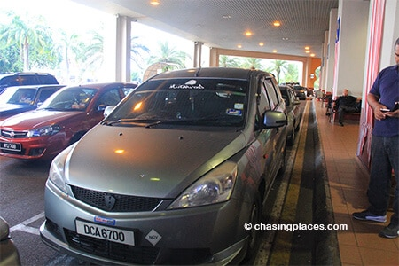 The taxis at Kota Bharu Airport are grey and located directly outside the exit