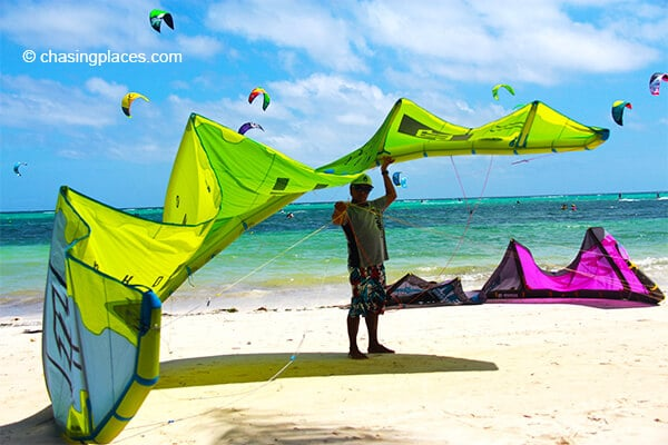 A local trainer preparing a kite while seeking some shade.